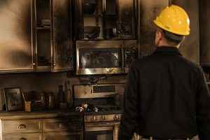 technician looking at fire damage in a kitchen