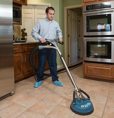 technician cleaning a kitchen floor