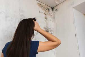 alarmed woman looking at black mold on wall