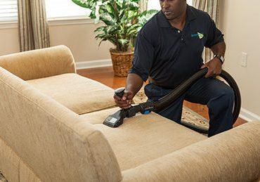technician cleaning a sofa
