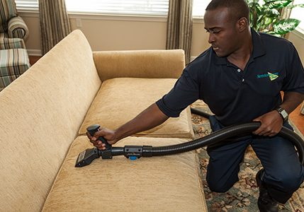 technician cleaning sofa